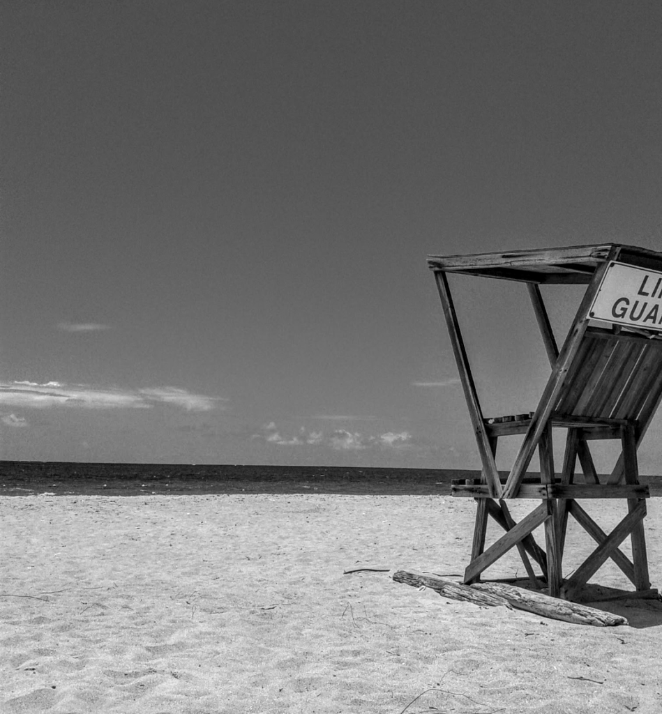 Picture of beach, sea and sky. angled looking at sea horizon. with back shot of chair for life guards facing the sea.