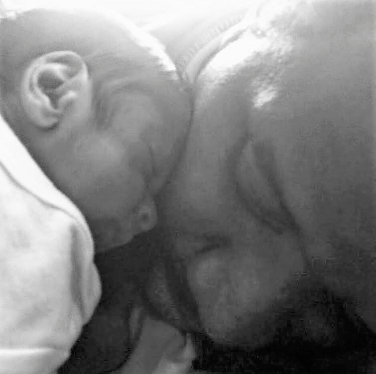 baby resting head on man's cheek. father and son.